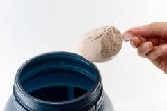 El aumento de la mano un polvo del chocolate de la proteína de la medida de la cuchara para Imagen de archivo libre de regalías