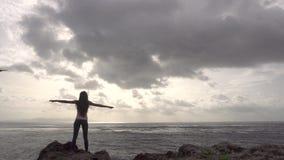 El aumento de la mujer del basculador da la situación en roca cerca del océano almacen de video