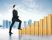 El aumento en concepto de los beneficios con el hombre de negocios sube las escaleras o fotografía de archivo
