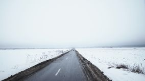 El auto juguetón rojo comienza a conducir en el camino rodeado por los campos cubiertos en nieve almacen de metraje de vídeo