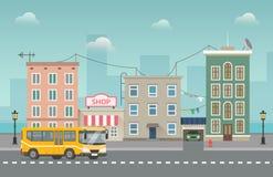 El autobús amarillo circunda la pequeña ciudad con las tiendas y la costa detrás Paisaje urbano Foto de archivo