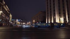 El autobús Bendy pasa la intersección ciudad de la noche del fondo, arquitectura majestuosa almacen de video