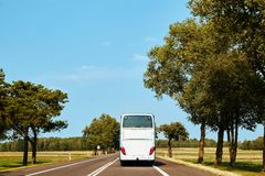El autobús interurbano blanco está conduciendo a lo largo del camino imágenes de archivo libres de regalías