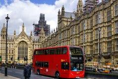 El autobús rojo de Londres delante de las casas de Westminster del parlamento foto de archivo libre de regalías
