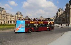 El autobús turístico conduce más allá del Louvre en París, Francia fotos de archivo