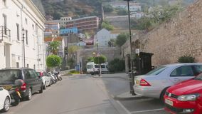 El autobús turístico está conduciendo en las calles de Gibraltar El guía turístico habla de objetos de visita turístico de excurs metrajes