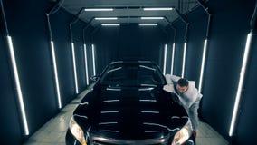 El automóvil está consiguiendo pulido por un trabajador de sexo masculino almacen de video