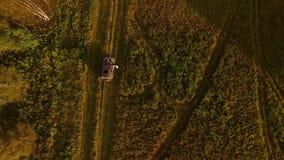 El autostopista cogió el coche en campo en el camino rural cantidad La vista superior del coche, en eso se sienta al autostopista almacen de metraje de vídeo