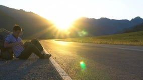 El autostopista se sienta en el borde de la carretera en las montañas con una tableta a disposición, inclinándose en una mochila metrajes