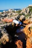 El aventurero agotado bebe el agua de una grieta en una roca fotografía de archivo libre de regalías