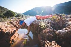 El aventurero agotado bebe el agua de una grieta en una roca fotos de archivo libres de regalías