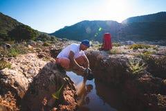 El aventurero agotado bebe el agua de una grieta en una roca fotos de archivo