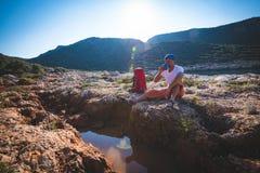 El aventurero agotado bebe el agua de una grieta en una roca fotografía de archivo