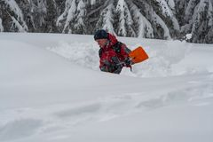 El aventurero cava una cueva en la nieve durante las nevadas foto de archivo