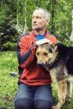 El aventurero del hombre con el perro grande está descansando en el bosque imagen de archivo libre de regalías