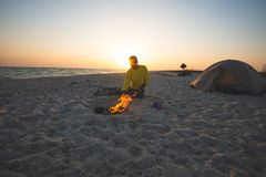 El aventurero se sienta al lado de hoguera ardiente en la playa fotos de archivo libres de regalías
