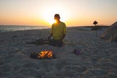 El aventurero se sienta al lado de hoguera ardiente en la playa fotografía de archivo libre de regalías