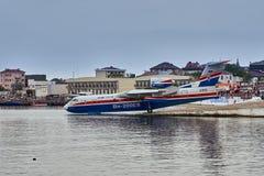 El avión anfibio multiusos ruso Beriev Be-200ES recolecta el agua y se está preparando para sacar de la superficie lisa fotografía de archivo