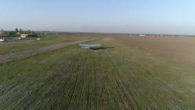 El avión azul saca sobre campo contra línea del cielo y del horizonte en primavera metrajes