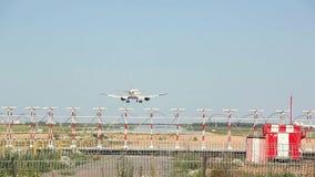 El avión blanco aterriza en la pista en el fondo del aeropuerto almacen de metraje de vídeo