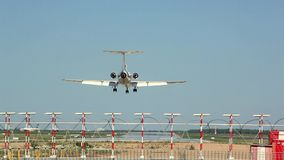 El avión blanco aterriza en la pista en el fondo del aeropuerto metrajes