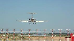El avión blanco aterriza en la pista en el fondo del aeropuerto almacen de video