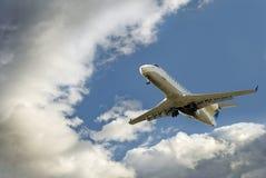 El avión comercial desciende de los cielos que amenazan Fotografía de archivo