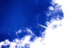 El avión corta las nubes y vuela en el cielo azul Vuelo del aeroplano imagen de archivo