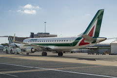 El avión de Alitalia y empuja detrás Fotos de archivo libres de regalías
