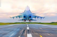 El avión de combate militar vuela en la velocidad sobre la pista de rodaje en el aeropuerto foto de archivo