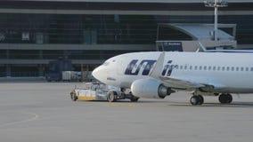 El avión de la línea aérea Utair se remolca a lo largo de la pista de rodaje almacen de metraje de vídeo