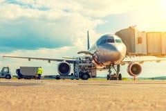 El avión de pasajero se está preparando para el vuelo en el aeropuerto en el sol poniente Foto de archivo