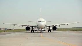 El avión de pasajeros blanco se está moviendo a lo largo de la pista de rodaje y está consiguiendo listo para sacar metrajes