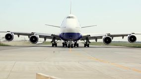 El avión de pasajeros blanco se está moviendo a lo largo de la pista de rodaje y está consiguiendo listo para sacar almacen de video