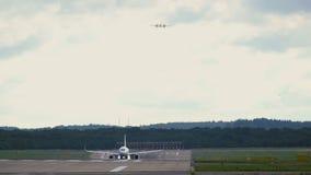 El avión de reacción saca Avión de negocio que se acerca a la misma pista almacen de video
