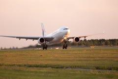 El avión de salida de MASkargo Airbus A330-223F en la puesta del sol irradia Foto de archivo