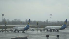 El avión del aeroplano del pasajero, avión, jet cerca del terminal en un aeropuerto aguarda el embarque del pasajero en el termin almacen de metraje de vídeo