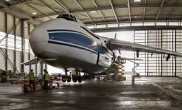 El avión en el avión de carga ruso más grande Ruslan del ` s del mundo del puerto- y la gente que trabaja en él Imagen de archivo libre de regalías