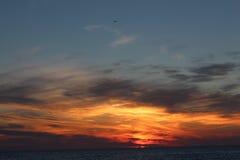 El avión en el fondo de una puesta del sol hermosa en el mar en el complejo playero arenoso Fotografía de archivo