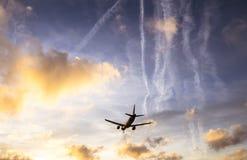 El avión está aterrizando durante una puesta del sol agradable Imagen de archivo libre de regalías