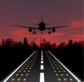El avión está sacando en la ciudad de la puesta del sol y de la noche Imagen de archivo libre de regalías
