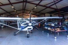 El avión ligero acepilla el taller del hangar Imagenes de archivo