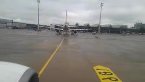 El avión se mueve con la opinión del aeropuerto a través de la ventana de los aviones Aeroplano en el aeropuerto almacen de metraje de vídeo