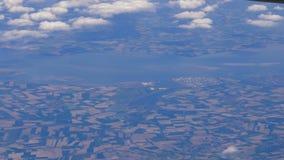 El avión vuela altamente sobre la tierra y las nubes