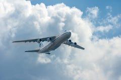 El avión vuela contra un fondo de las nubes de cúmulo y del cielo azul Fotos de archivo libres de regalías