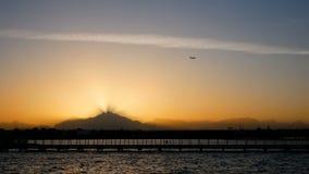 El avión vuela sobre la puesta del sol sobre las montañas Los rayos de la luz pasan a través del mar tranquilo y del embarcadero  almacen de metraje de vídeo