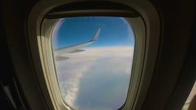 El avión vuela sobre las nubes, visión a través de la ventana al ala de un aeroplano del pasajero metrajes