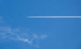 El avión y su pista torsional en el fondo del cielo azul Fotos de archivo