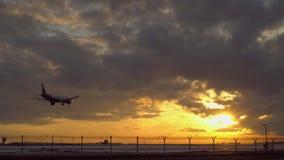 El avi?n est? aterrizando La puesta del sol, otro avión saca en el cielo en el fondo almacen de video