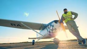 El aviador de sexo masculino alegre es que viene y permanente al lado de un aeroplano almacen de metraje de vídeo
